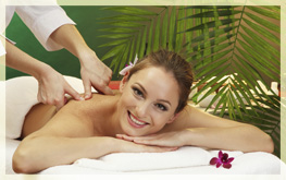 beautiful woman in spa salon with stones getting massage, on gre